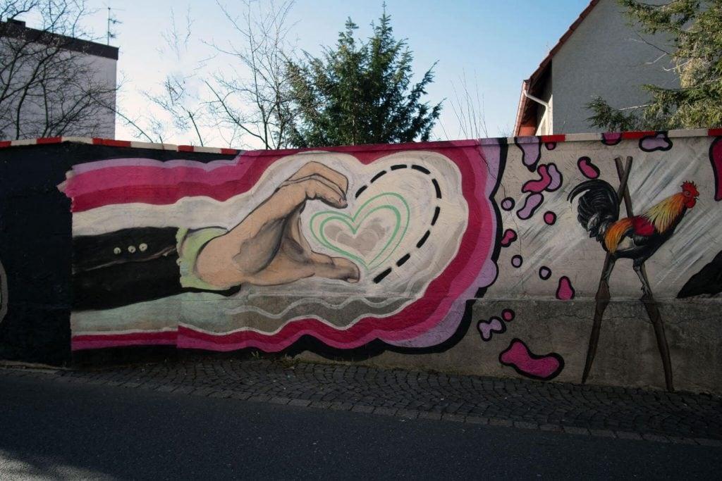 Busdorfmauer - Kunst zeigt einen halben Herzen einer Hand die vervollständigt werden will